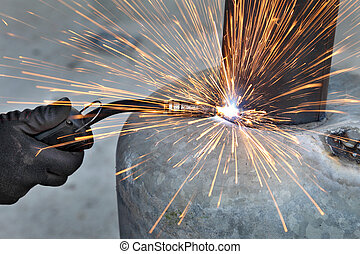 Welding - Arc welding of a steel, welder hands in gloves,...