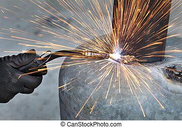 Welding - Arc welding of a steel, welder hands in gloves,...