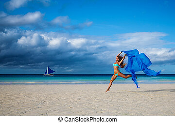 Beautiful young woman jumping on the beach with a blue...