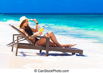 young woman in straw hat laying at the tropical beach and...