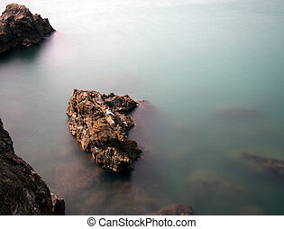 Rocky shoreline with gull and submerged rocks, silky water...