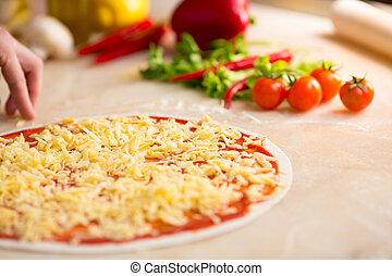 Italian pizza preparation. Cheese covering.