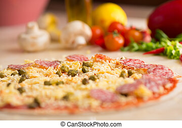 raw italian salami pizza on table with ingredients