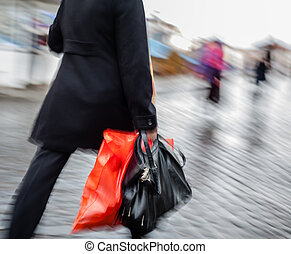 woman walking down the street in the rain with a red package...