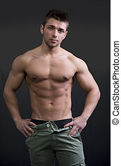 Muscular young man shirtless in relaxed pose on dark...