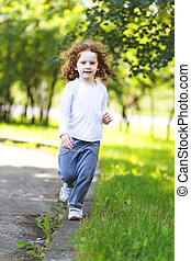 Little girl runs in the spring park.