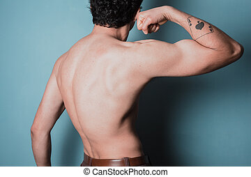 Muscular young man flexing his bicep - Rear view of a...