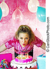 Teen girl Blowing out Candles - Young teen girl blows out...