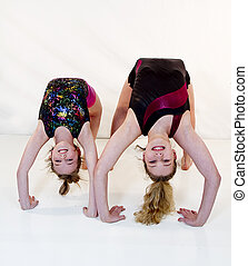 Girls Up-side Down in Gymnastics - Two youg girls in...