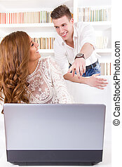casual young man showing something to his pretty wife on a screen in their living room