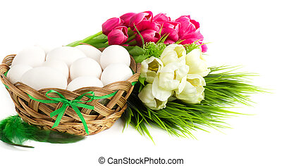 Basket with Easter eggs and spring flowers on white...