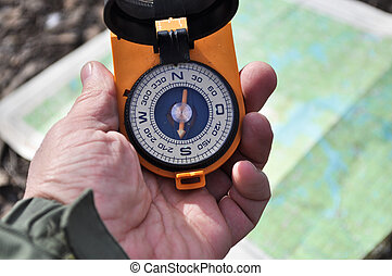 The compass in his hand outdoors. - Magnetic compass in the...