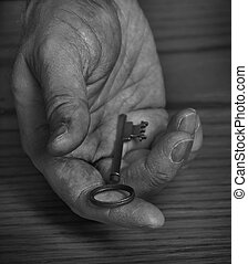 Hand Holding Old Key Giving Away - Old hand holding and...