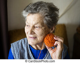 Senior woman knitting - Portrait of senior woman sitting in...