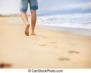 Man wallking at the beach - Detail of male feet walking at...