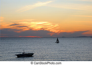 Two Sailboats in the Sea at Sunset