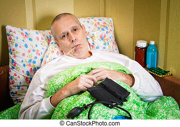 Sick Man in Bed with Thermometer - Sick man lying in bed and...
