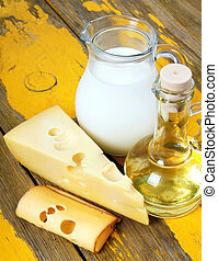 Oil and cheese on wooden board - Dairy products on a wooden...