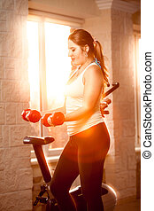 Woman at gym training with dumbbells at sunset