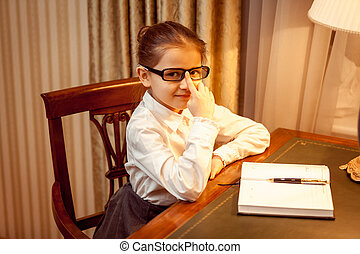 Girl in eyeglasses sitting behind table with notebook