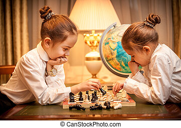 Girls in school uniform playing chess at cabinet