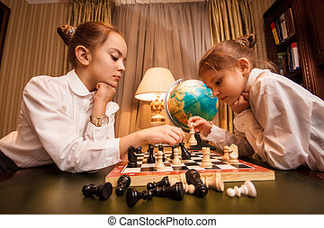 two little sisters playing chess - Portrait of two little...