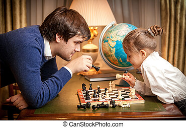Handsome man playing chess with girl