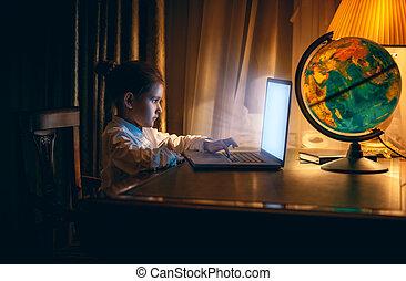 Little girl doing homework on laptop at evening - Portrait...