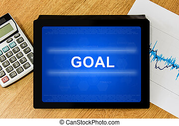 goal word on digital tablet with calculator and financial...