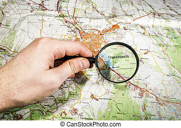 The toe points to the city of Somferopol? on the map of Crimea,The finger points at a map of the area