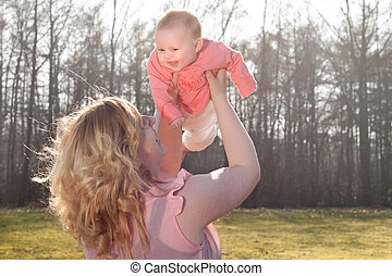 Baby flying in nature when mommy is holding her - Mother and...