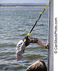 suspension training at the sea - hooded man...