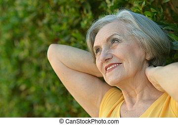 Happy elderly woman in summer green park