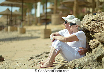 Older couple in sunglasses sitting on beach