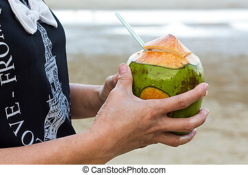 Woman hand holding coconut.