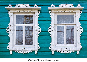 Wooden platbands on two window of an village house - Wooden...