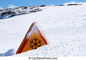 snow danger sign covered in snow