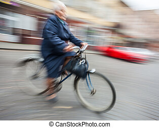 woman rides a bicycle through the streets - Abstract image...