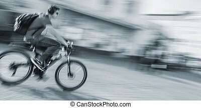 Young man riding a bicycle on the street - Young man with...