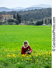 young girl collecting flowers on green grass field