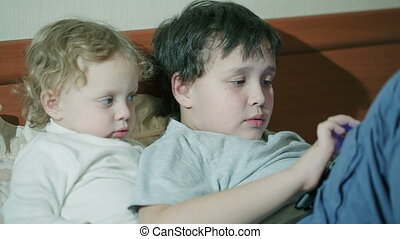 Two young children playing with a tablet computer as they...