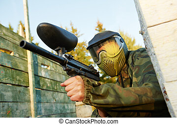 paintball player in prootective uniform and mask aiming and...