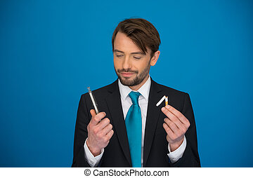 handsome businessman holding broken cigarette and...