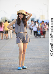young and pretty asian woman wearing straw hat standing and...