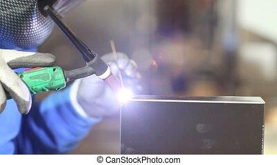 hands of worker welding in factory