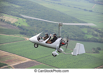 Autogyro flying over the tropical landscape