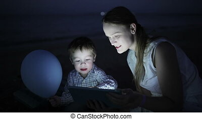 Kid with mom on the beach at night - Cute kid and his mother...