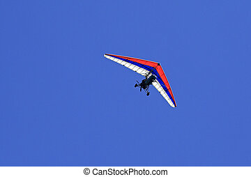 Trike hang glider with a motor against the blue sky