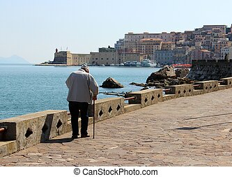 Old man walking - An old man walking with a cane on the...