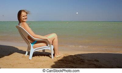 Sunbathing on the beach - Young woman sunbathing sitting on...